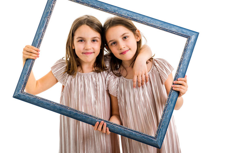 Identical twin girls are making happy expressions with picture frame. Children, sisters, girls posing in studio with picture frame, making different facial expressions. Family portrait, frontal view. Adorable Background Beautiful Casual Caucasian Cheerful Child Childhood Concept Cute Dress Emotions Empty Expression Face Family Fashion Frame Friendship Fun Girls Hair Happiness Happy Holding Identical  IDENTICAL TWINS Isolated Joyful Kids Laughing Lifestyle Little Looking person Photo Picture Portrait Posing Siblings Sisters Smile Smiling Studio Together Twins Two White Young