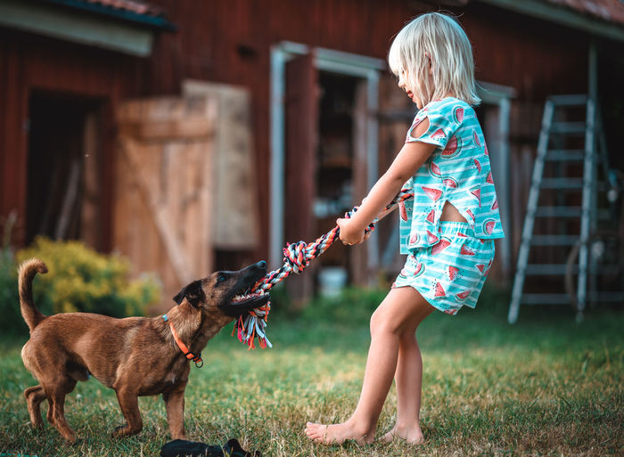 Full length side view of girl playing with dog in lawn