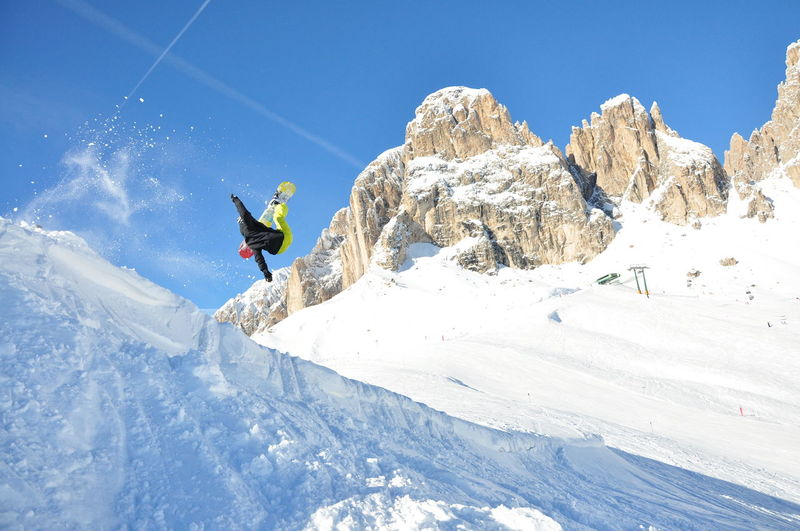 Man snowboarding on snow against sky