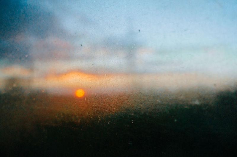 Defocused image of wet glass window during sunset