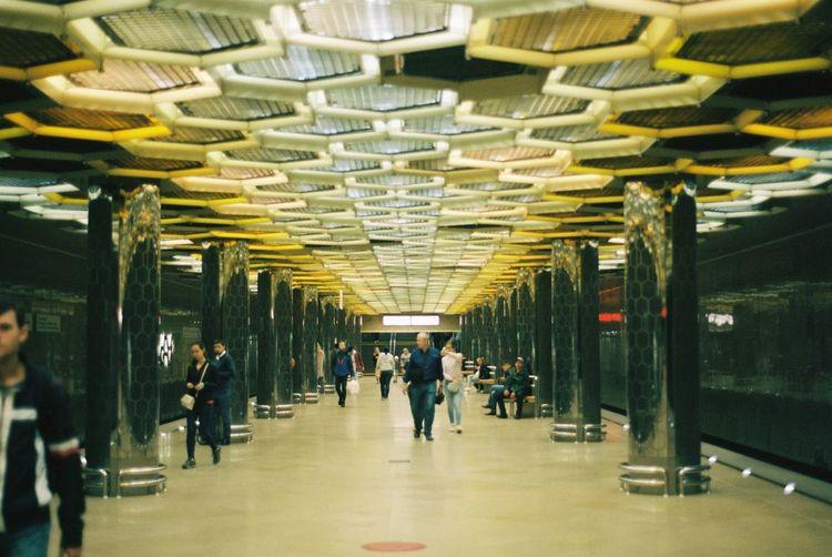 People walking on illuminated railroad station platform