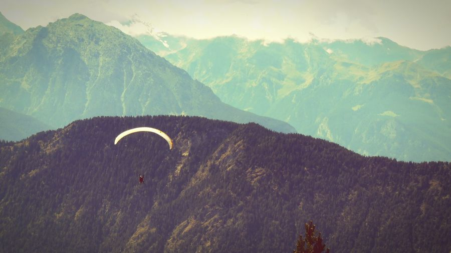 Person paragliding by mountains