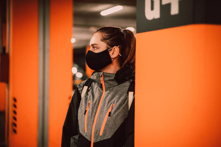 Young woman standing against orange wall