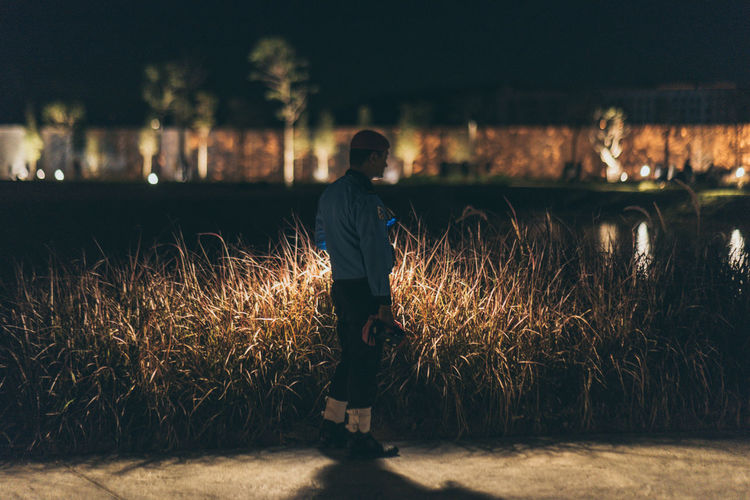 A guard in a park Night Nature Real People Men Walking Rear View Field Standing Outdoors Plant Land Adult Lifestyles Full Length One Person Casual Clothing Leisure Activity Young Men Focus On Foreground EyeEm Selects
