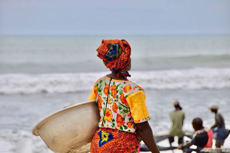 Rear view of woman with container standing on beach