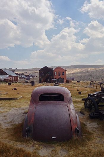 This place is a ghost town! Bodie Ghost Town Rusted Car Abandoned Houses Desert Weeds Dirt Old Car Old Machinery Distant Sky Clouds And Sky Landscape Travel Destinations Day Outdoors Tranquility Horizon Over Land Room For Copy