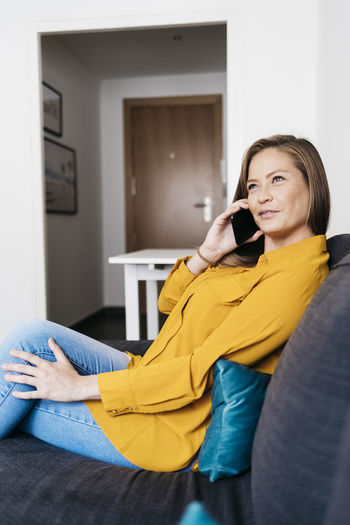 Young woman talking over mobile phone while sitting on sofa at home