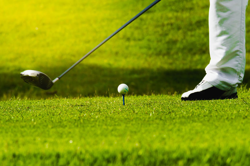 Low section of man playing golf on grass