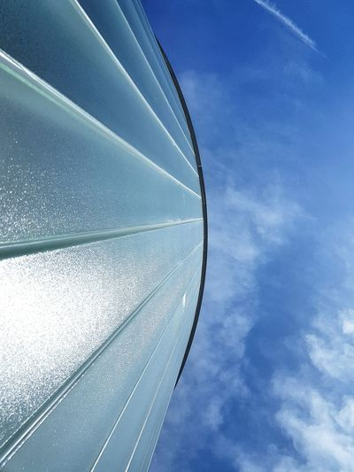 Low angle view of glass against blue sky
