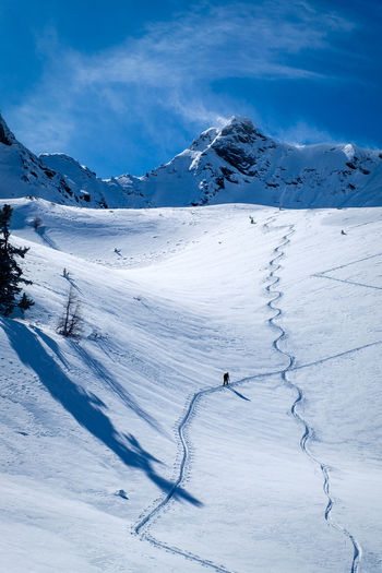 Man Walking On Snowcapped Mountain