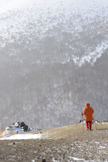 Rear view of man walking on hill during winter