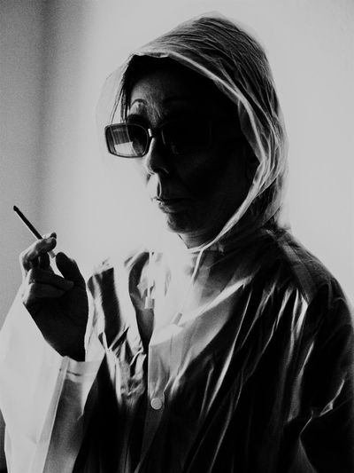 Woman wearing raincoat and sunglasses while smoking cigarette
