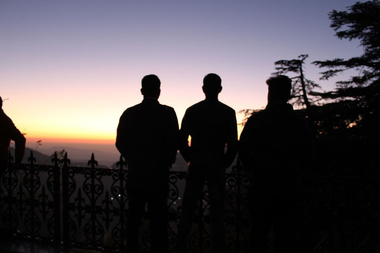 Rear view of silhouette people standing against sky during sunset