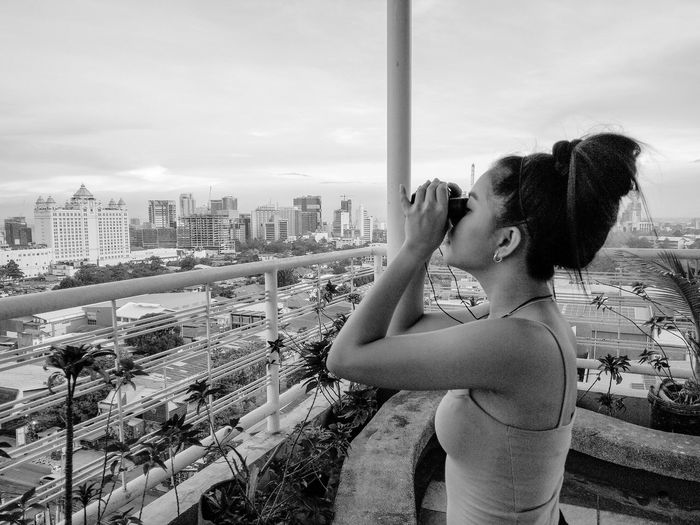 Side view of woman standing by railing against sky
