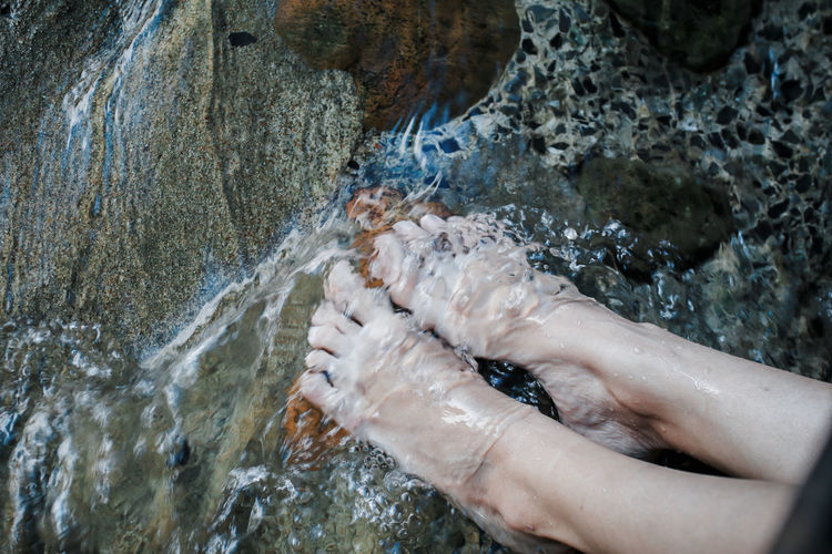 Low section of woman feet in stream