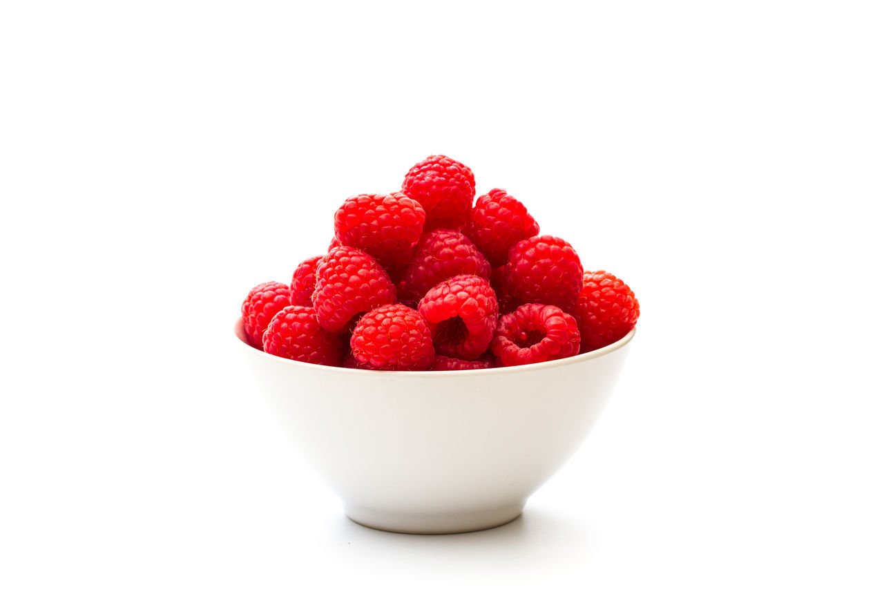 Close-Up Of Raspberries In Bowl Against White Background