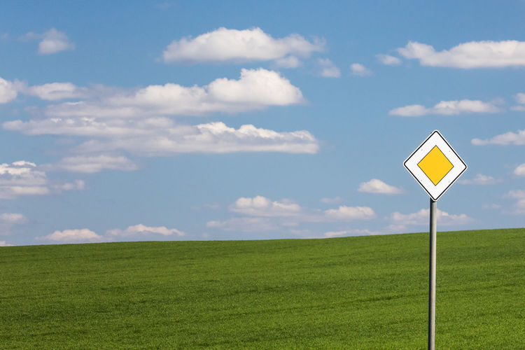 Road Sign On Grassy Field Against Sky