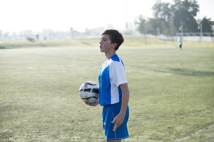 Rear view of boy playing soccer ball on grass