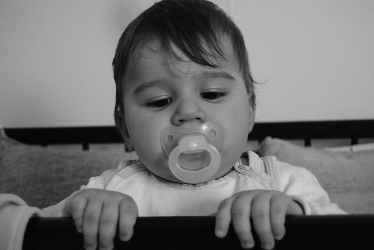 Close-up of baby boy with pacifier in mouth at home