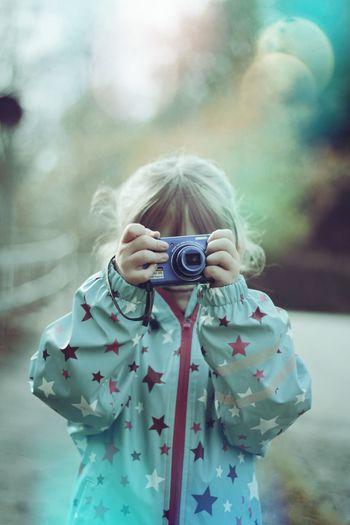 Close-Up Of Girl Photographing With Camera Outdoors