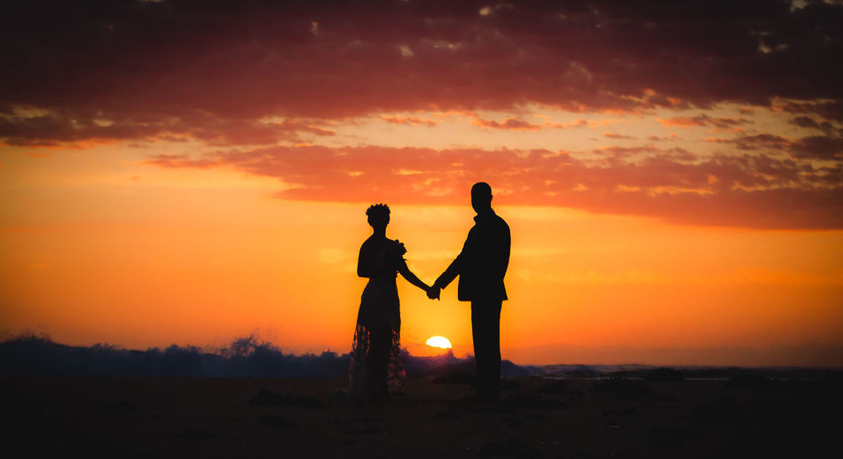 Silhouette Couple Standing At Beach Against Sky During Sunset