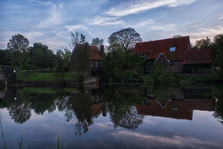 Evening reflections Tranquility Outdoors Day Residential District No People Waterfront Nature Lake Plant House Tree Water Sky Cloud - Sky Building Built Structure Architecture Building Exterior Reflection Symmetry