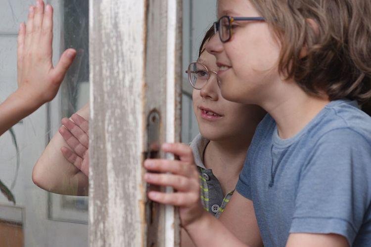 Boys standing by window