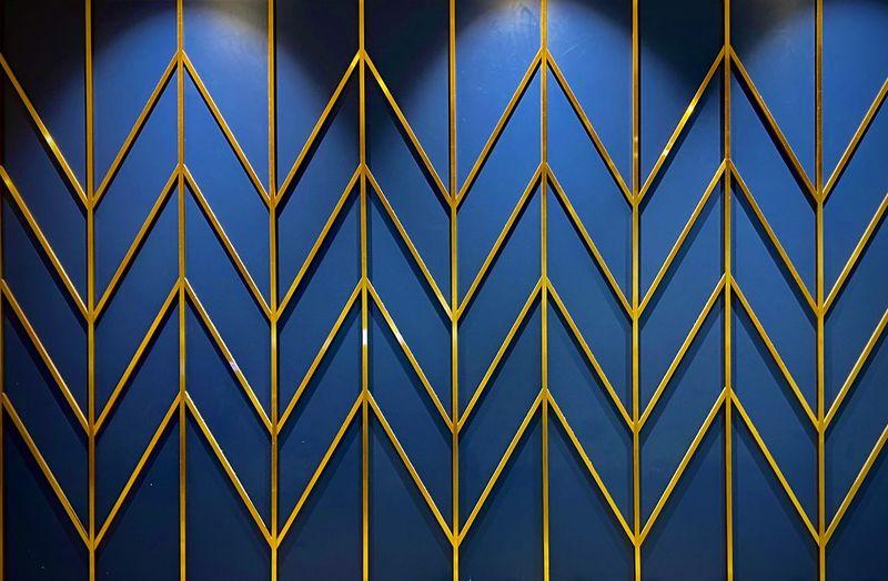 Full frame shot of metal fence against blue wall