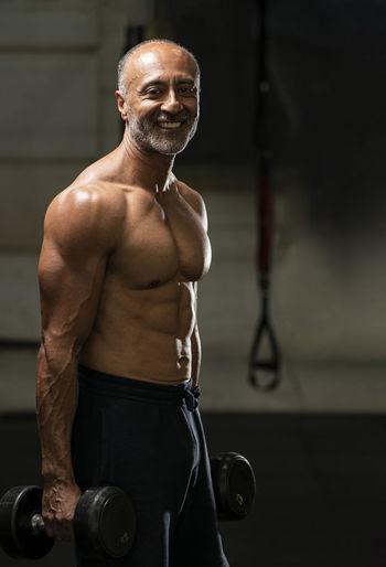 Portrait of shirtless man looking at camera