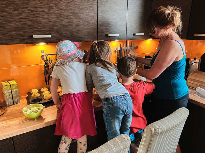 Rear view of family making food in kitchen at home