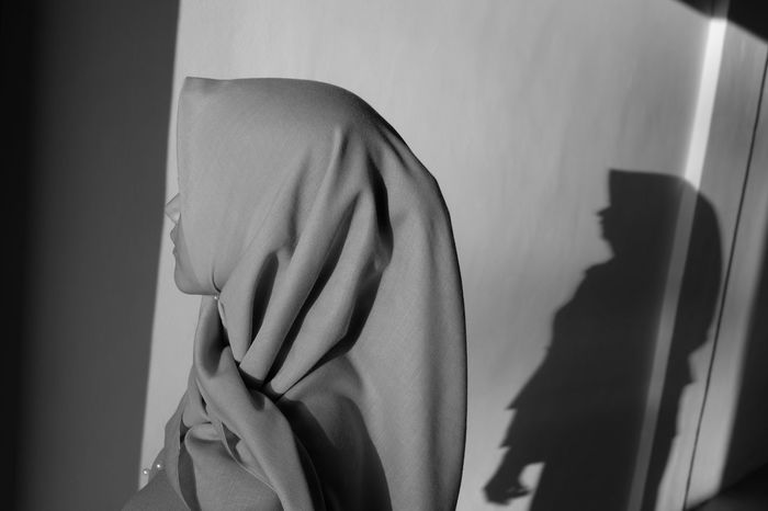 Close-up of woman wearing hijab against wall