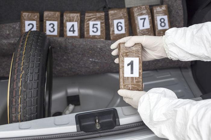 Drug smuggling. Drug bundles smuggled in a car trunk. Adult Car Trunk Close-up Crime Crimea Criminal Day Evidence Human Hand Illegal Indoors  Number One Person Packets People Police Smuggling Substance Trafficking Vehicle Working