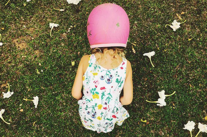 Rear view of girl wearing pink helmet while bending on grassy field