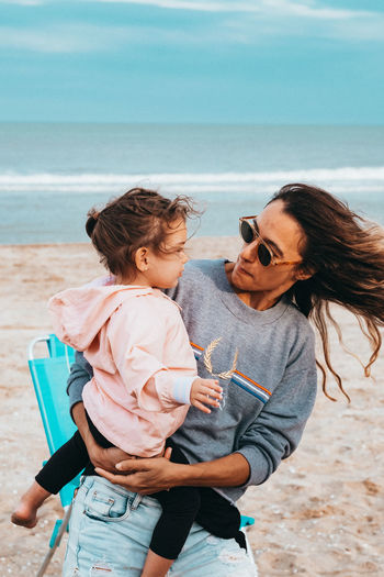 Woman carrying daughter while standing at beach