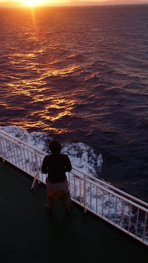 High angle view of man standing by railing and sea during sunrise