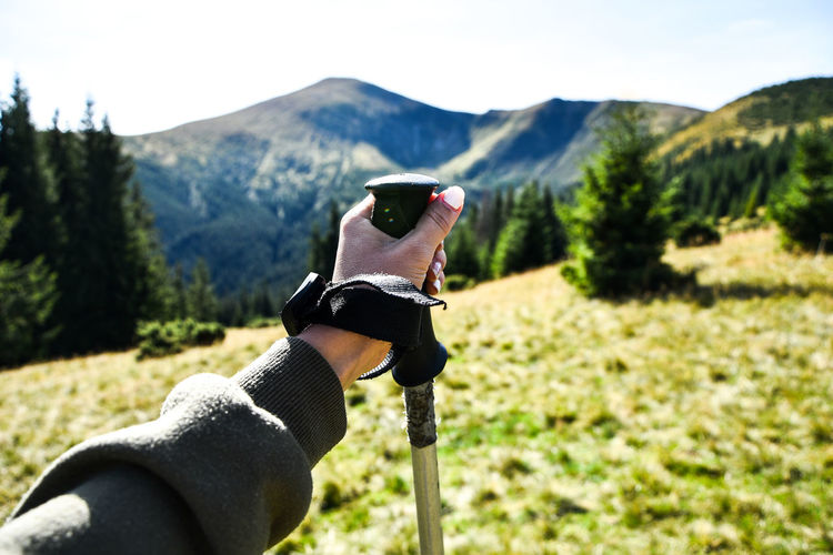 Trekking poles at top of mountain with beautiful view of autumn mountains. natural background. hand