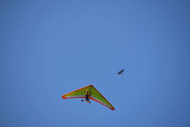 Low Angle View Of Man Hang Gliding In Clear Blue Sky