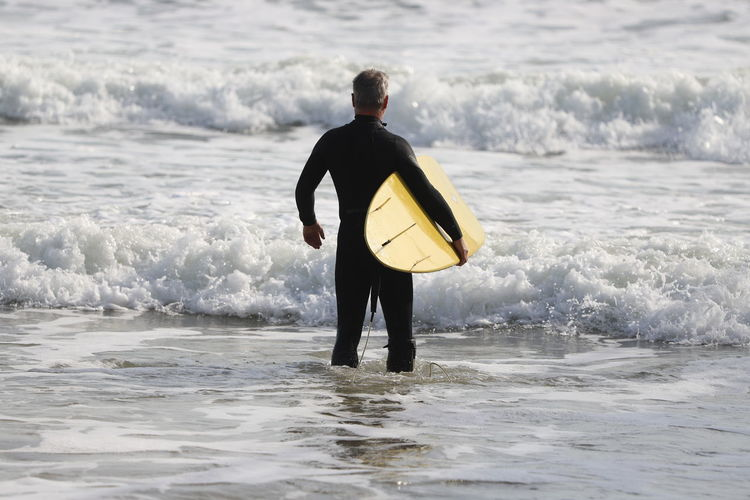 Rear View Of Male Surfer Standing In Sea