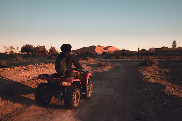 Rear view of man riding motorcycle at sunset