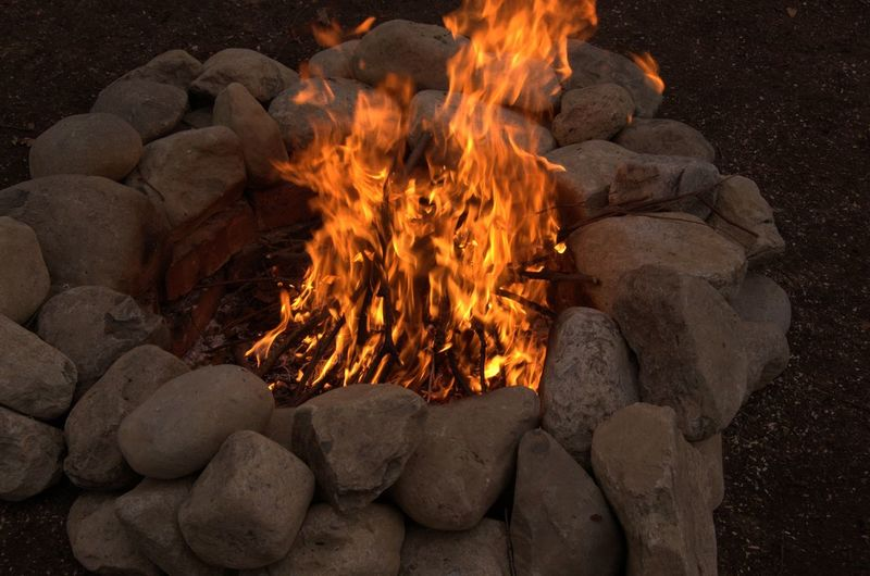 Blurred Motion Of Burning Campfire Amidst Stones