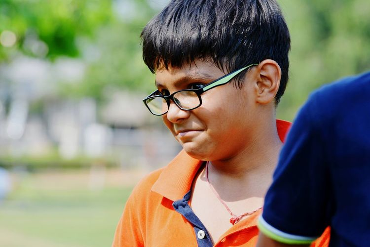 Boy wearing eyeglasses while looking away by friend at park