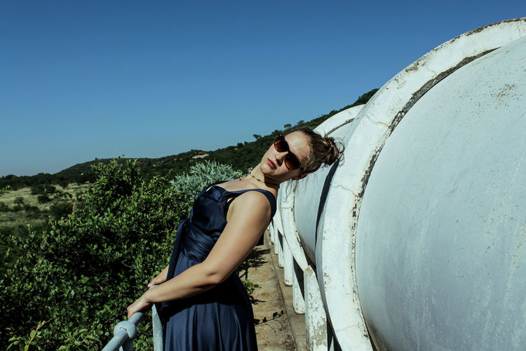 Portrait of young woman standing by pipes against clear blue sky
