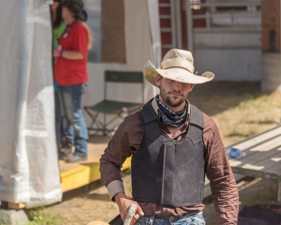 Williams Lake, British Columbia/Canada - July 2, 2016: cowboy walks toward arena to compete in the Wild Horse Race at the 90th Williams Lake Stampede, one of the largest stampedes in North America 90th Williams Lake Stampede Arena Behind The Scenes British Columbia, Canada Cariboo Chilcotin Cowboy Man Rodeo Rugged Travel Wild Horse Race Annual Event Candid Competition Competitor Cowboy Hat Danger Documentary Editorial  Extreme Sport Horse Race Male Portrait Professional Rodeo Stampede