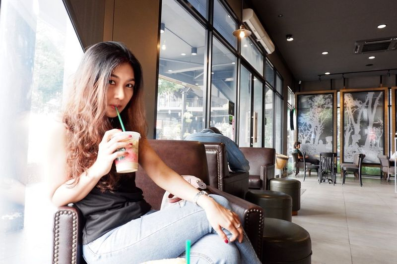 thai girl 134112 Sitting Young Adult One Person Indoors  Young Women Lifestyles Window Food And Drink Leisure Activity Relaxation Real People Three Quarter Length Women Adult Drink Casual Clothing Cafe Communication Drinking Contemplation