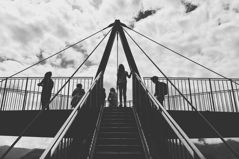 Low Angle View Of People On Footbridge Against Cloudy Sky