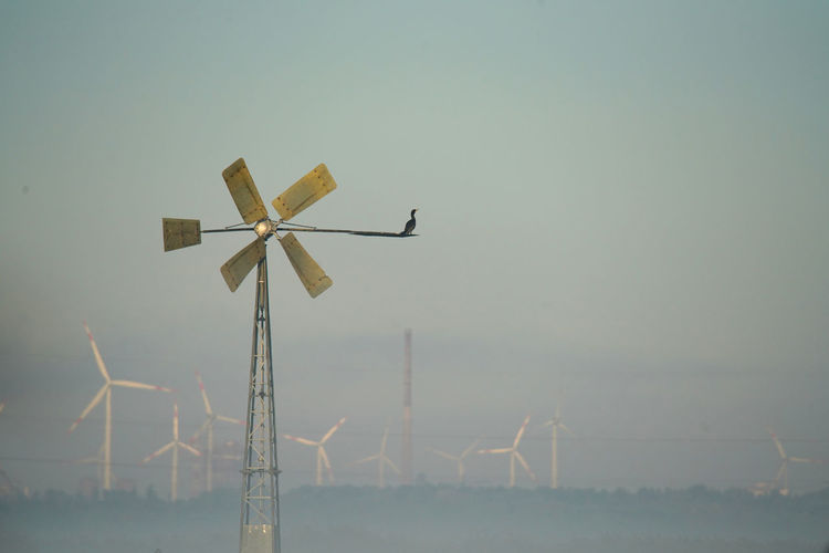 Low angle view of wind turbines on landscape against sky