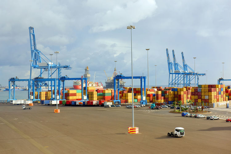 Cargo containers at commercial dock against cloudy sky