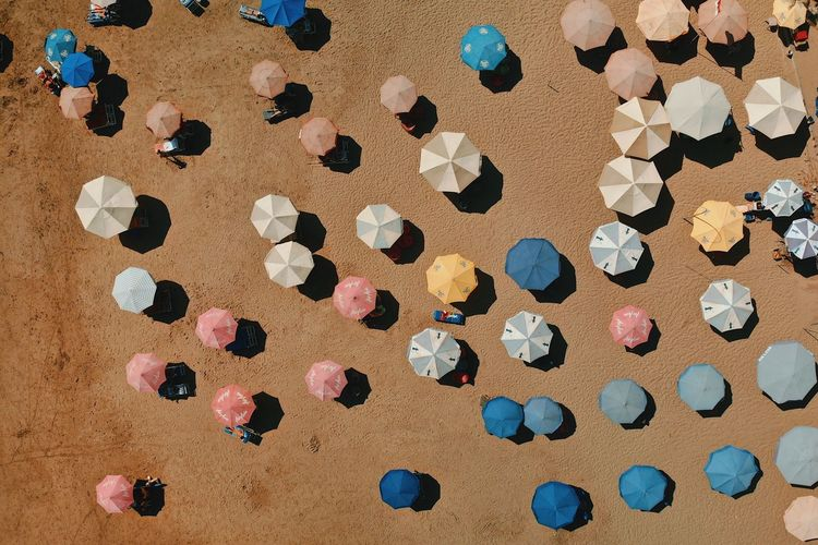 High Angle View Of Multi Colored Beach Umbrellas On Sand