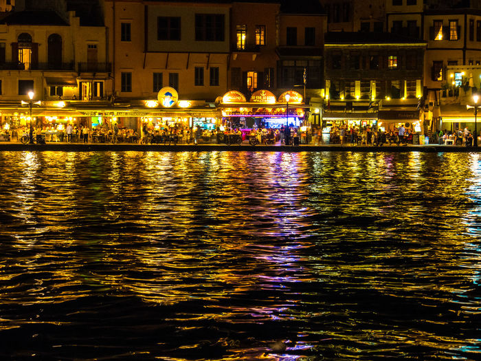 Lights from cafes and restaurants reflected in Chania Old Harbour at night Chania Old Port Illuminated Night Nightlife Reflection Travel Destinations Water Waterfront