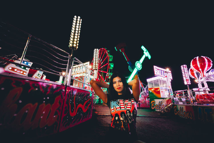 Portrait of girl with illuminated carousel against sky at night